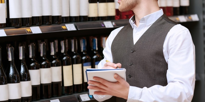 Young sommelier in a waistcoat making notes in his note pad standing by wine shelves and looking at the labels on bottles
