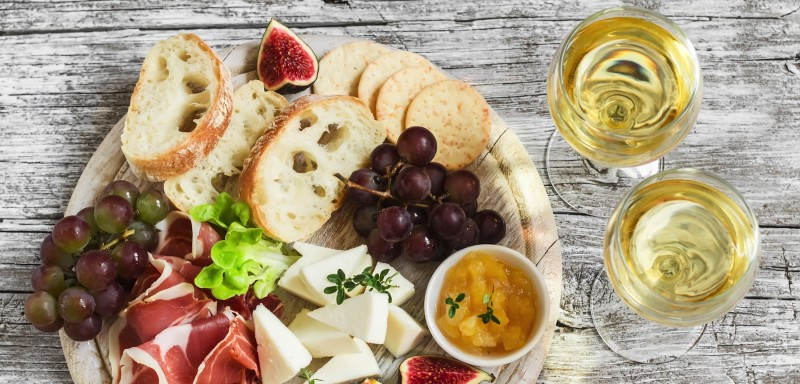 Delicious Appetizer To Wine - Ham, Cheese, Grapes, Crackers, Figs, Nuts, Jam, Served On A Light Wood